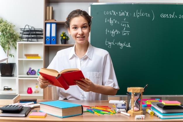 Sorridente giovane insegnante di matematica femminile bionda seduta alla scrivania con gli strumenti della scuola che tiene il libro in aula