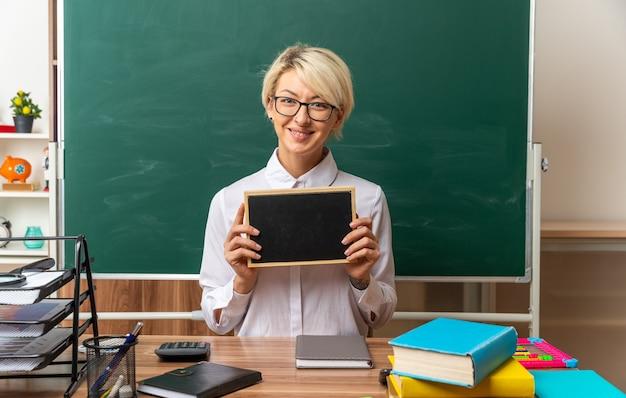 Sorridente giovane insegnante bionda con gli occhiali seduto alla scrivania con gli strumenti della scuola in aula guardando la telecamera che mostra la mini lavagna