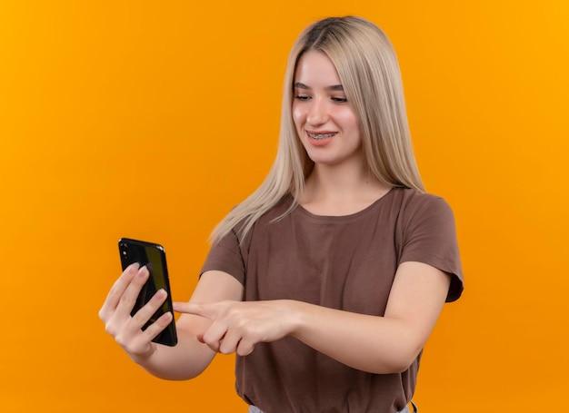 Sorridente giovane ragazza bionda in parentesi graffe dentale che tiene il telefono cellulare e toccandolo con il dito sullo spazio arancione isolato