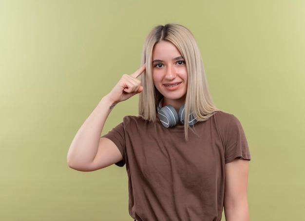 Sorridente giovane ragazza bionda in parentesi graffe dentali che indossano le cuffie sul collo con il dito sul tempio su uno spazio verde isolato