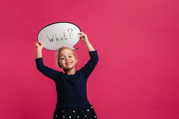 Smiling young blonde girl holding speech bubble and looking at the camera over pink wall