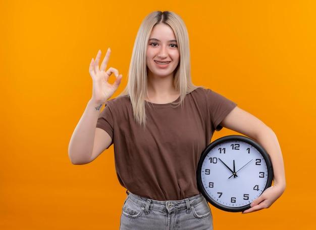 Улыбающаяся молодая блондинка в зубных скобах, держащая часы, делает хорошо, знак на изолированном оранжевом пространстве с копией пространства