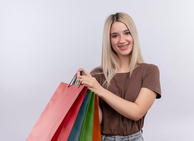 孤立した白いスペースに買い物袋を保持している歯科ブレースで若いブロンドの女の子の笑顔