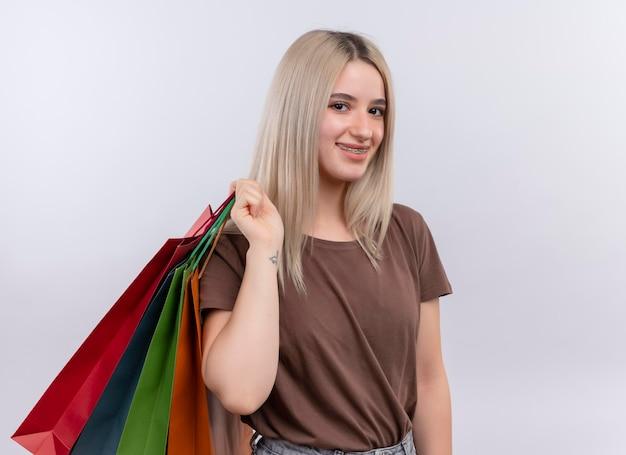 コピースペースと孤立した白いスペースで肩に買い物袋を保持している歯ブレースで笑顔の若いブロンドの女の子