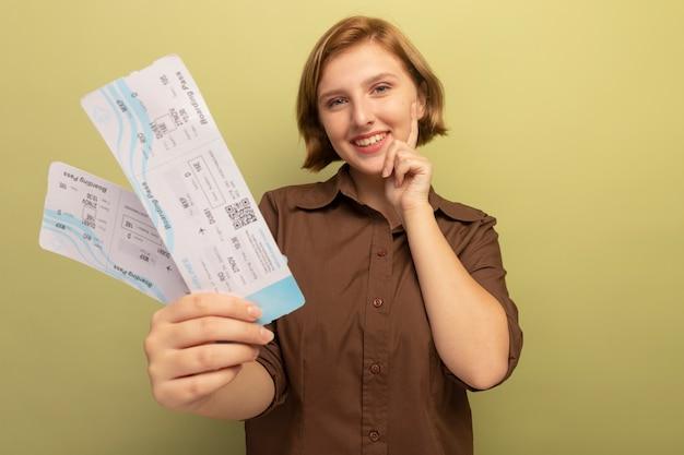 웃는 어린 금발 소녀가 복사 공간이 있는 올리브 녹색 벽에 격리된 턱에 손을 대고 카메라를 향해 비행기 표를 뻗고 있습니다.
