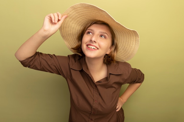 Smiling young blonde girl wearing beach hat grabbing hat keeping hand on waist looking at side isolated on olive green wall with copy space