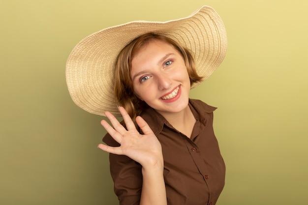 Sorridente giovane ragazza bionda che indossa cappello da spiaggia in piedi in vista di profilo guardando ondeggiante isolata sulla parete verde oliva con spazio di copia