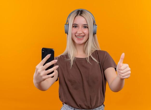 Улыбающаяся молодая блондинка в наушниках в брекетах держит мобильный телефон и показывает палец вверх на изолированном оранжевом пространстве