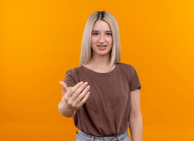 Sorridente giovane ragazza bionda con parentesi graffe dentali facendo venire qui gesto sullo spazio arancione isolato con spazio di copia