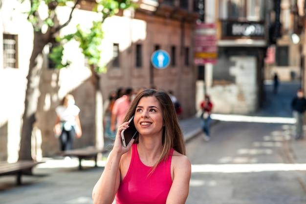 도시 주위를 산책 하 고 휴대 전화에 긴 머리를 가진 젊은 금발 소녀 미소.