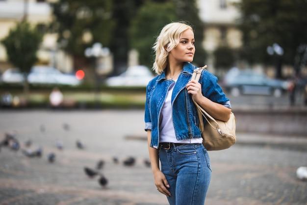 Улыбающаяся молодая блондинка женщина на уличном квадратном фонтане, одетая в синие джинсы с сумкой на плече в солнечный день