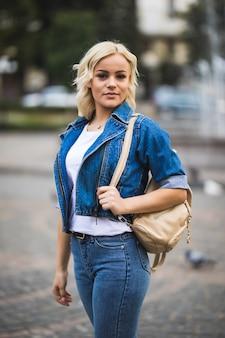 Улыбающаяся молодая блондинка женщина на уличном квадратном фонтане, одетая в джинсовый люкс с сумкой на плече в солнечный день