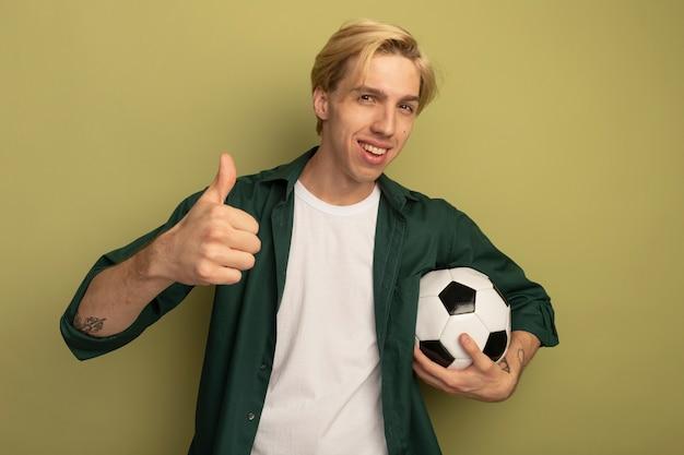공을 들고 엄지 손가락을 보여주는 녹색 티셔츠를 입고 웃는 젊은 금발의 남자