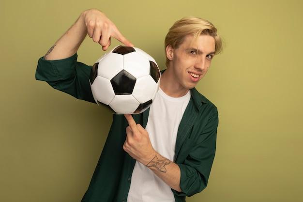 손가락에 공을 들고 녹색 티셔츠를 입고 웃는 젊은 금발의 남자
