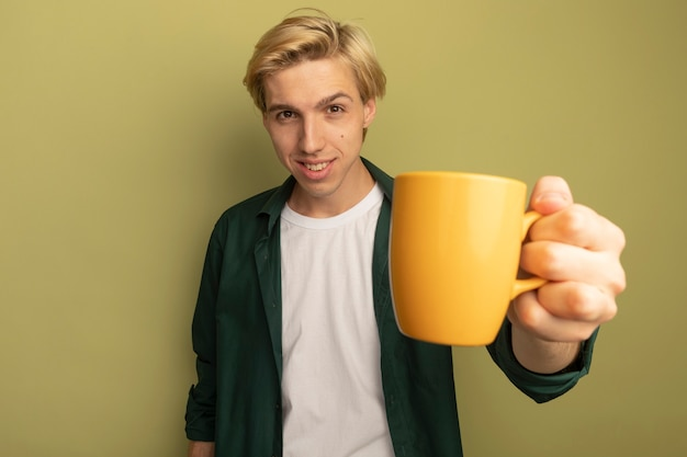 Smiling young blonde guy wearing green t-shirt holding out cup of tea