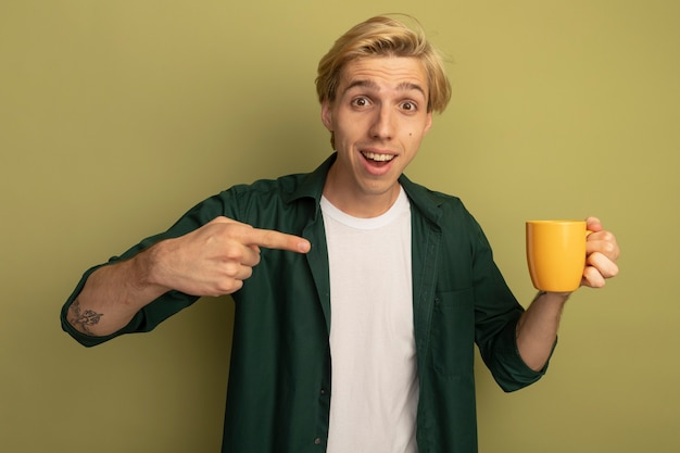 Smiling young blonde guy wearing green t-shirt holding and points at cup of tea