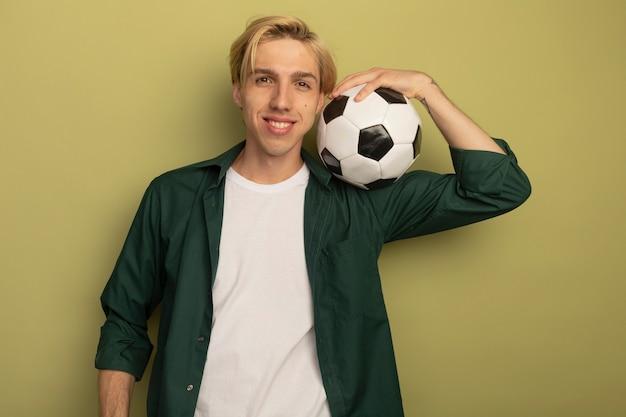 어깨에 공을 넣어 녹색 티셔츠를 입고 웃는 젊은 금발의 남자