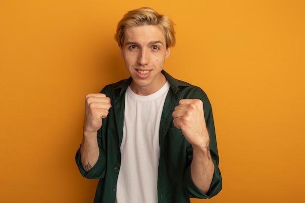 싸우는 포즈에 서있는 녹색 티셔츠를 입고 웃는 젊은 금발의 남자