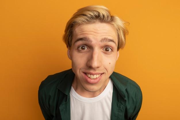 Улыбающийся молодой блондин в зеленой футболке