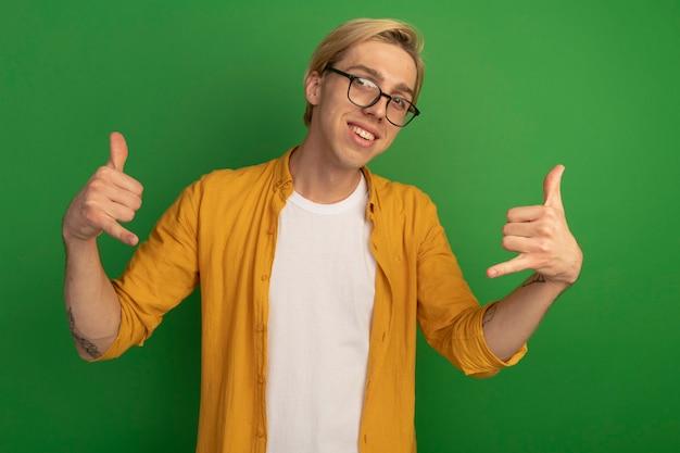 노란색 티셔츠와 녹색에 고립 된 전화 제스처를 보여주는 안경을 쓰고 웃는 젊은 금발의 남자