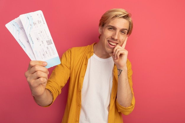 Sorridente giovane ragazzo biondo che indossa la maglietta gialla che tiene i biglietti mettendo la mano sulla guancia isolata sul rosa con copia spazio
