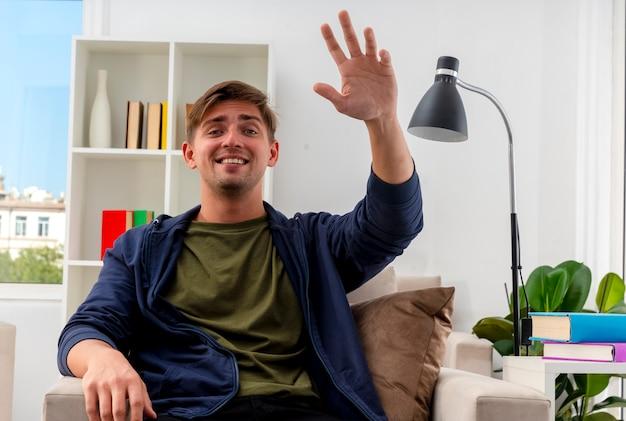 웃는 젊은 금발의 잘 생긴 남자는 안락의 자에 손을 들고 거실 내부에 카메라를보고 앉아