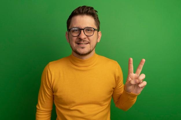 緑の壁に分離された平和のサインをやって探している眼鏡をかけて笑顔の若いブロンドのハンサムな男