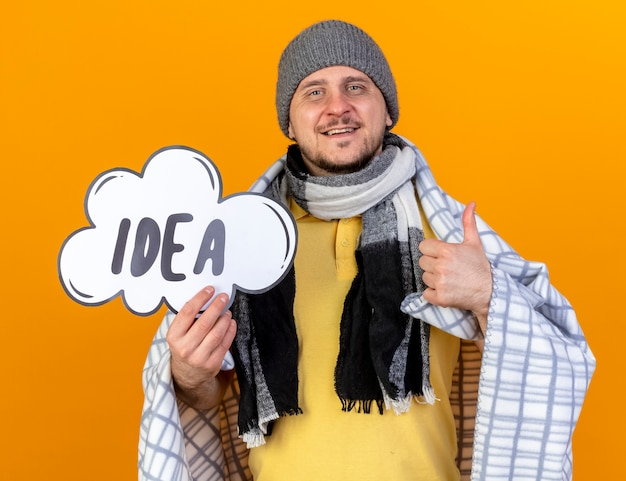 Smiling young blonde ill slavic man wearing winter hat and scarf wrapped in plaid thumbs up and holds idea bubble isolated on orange wall with copy space
