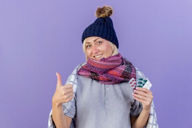 격자 무늬 엄지 손가락에 싸여 겨울 모자와 스카프를 착용하는 젊은 금발의 아픈 슬라브 여자 미소