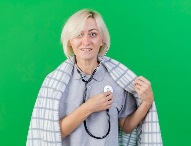 格子縞に包まれた笑顔の若いブロンドの病気のスラブ女性は、コピースペースで緑の壁に分離された聴診器を保持