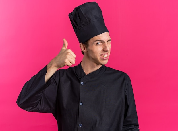 Smiling young blonde male cook in chef uniform and cap looking at camera winking showing thumb up isolated on pink wall