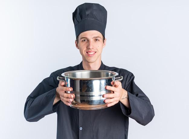 Улыбающийся молодой блондин мужчина-повар в униформе шеф-повара и кепке держит горшок, глядя в камеру, изолированную на белой стене