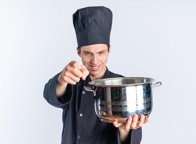 Улыбающийся молодой блондин мужчина-повар в униформе и кепке шеф-повара смотрит и указывает на камеру, протягивая горшок к камере, изолированной на белой стене
