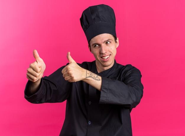 Улыбающийся молодой блондин мужчина-повар в униформе шеф-повара и кепке, глядя в сторону, показывает палец вверх, изолированный на розовой стене