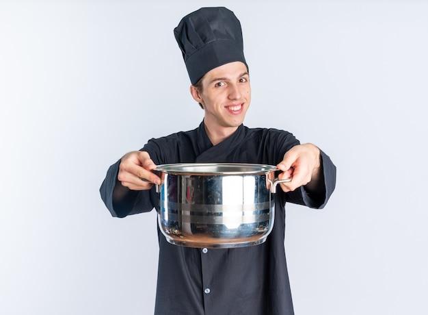 Улыбающийся молодой блондин мужчина-повар в униформе шеф-повара и кепке протягивает горшок к камере