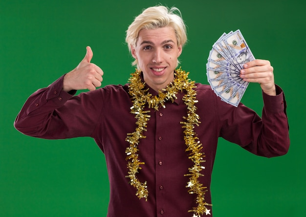 Smiling young blonde man wearing glasses with tinsel garland around neck holding money looking at camera showing thumb up isolated on green background