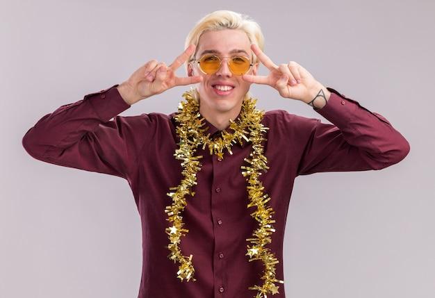 Sorridente giovane uomo biondo con gli occhiali con la ghirlanda di tinsel intorno al collo che mostra i simboli del segno di v vicino agli occhi isolati sulla parete bianca