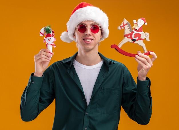オレンジ色の背景で隔離のカメラを見てロッキング馬の置物と甘い杖の飾りにサンタを保持しているサンタの帽子とメガネを身に着けている若いブロンドの男の笑顔