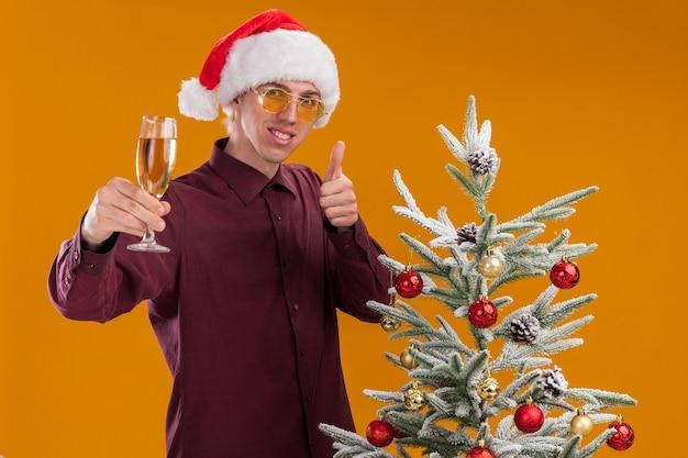 Улыбающийся молодой блондин в шляпе санта-клауса и очках стоит возле украшенной елки и протягивает бокал шампанского