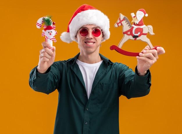 オレンジ色の背景に分離されたカメラを見てカメラに向かってロッキング馬の置物と甘い杖の飾りにサンタを伸ばしてサンタの帽子とメガネを身に着けている若いブロンドの男の笑顔