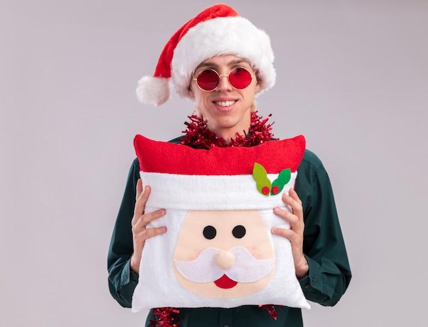 Улыбающийся молодой блондин в шляпе санта-клауса и очках с гирляндой из мишуры на шее, держа подушку санта-клауса, глядя в камеру, изолированные на белом фоне