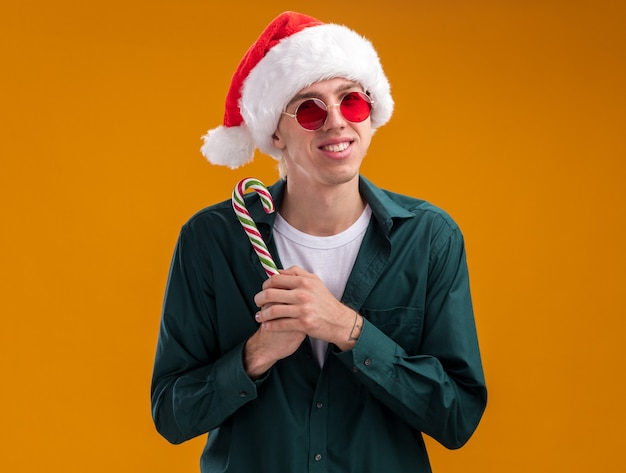 Smiling young blonde man wearing santa hat and glasses holding christmas sweet cane looking at camera isolated on orange background