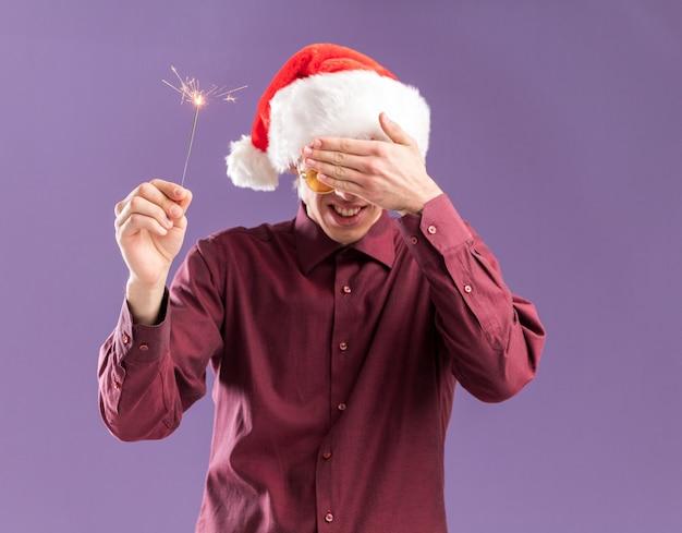 Sorridente giovane uomo biondo che indossa il cappello della santa e occhiali che tengono gli occhi scintillanti vacanza che copre con la mano isolato su sfondo viola