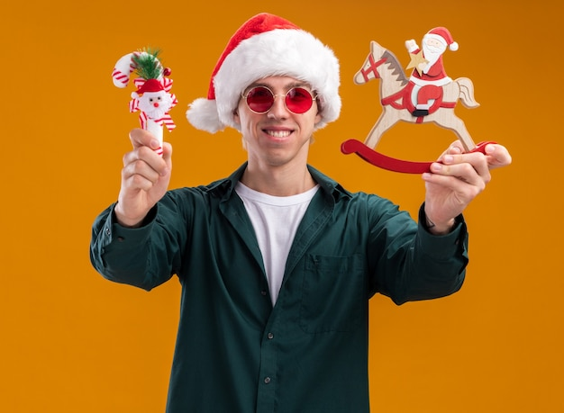 Smiling young blonde man wearing santa hat and glasses stretching out santa on rocking horse figurine and sweet cane ornament towards camera looking at camera isolated on orange background