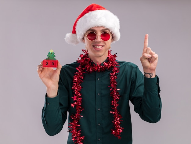 Smiling young blonde man wearing santa hat and glasses with tinsel garland around neck holding christmas tree toy with date looking at camera pointing up isolated on white background