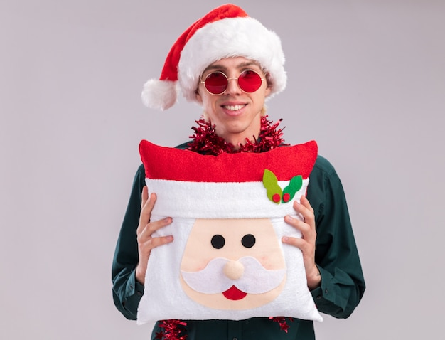 Smiling young blonde man wearing santa hat and glasses with tinsel garland around neck holding santa claus pillow looking at camera isolated on white background