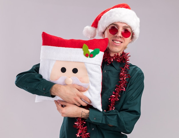 Smiling young blonde man wearing santa hat and glasses with tinsel garland around neck hugging santa claus pillow looking at camera isolated on white background
