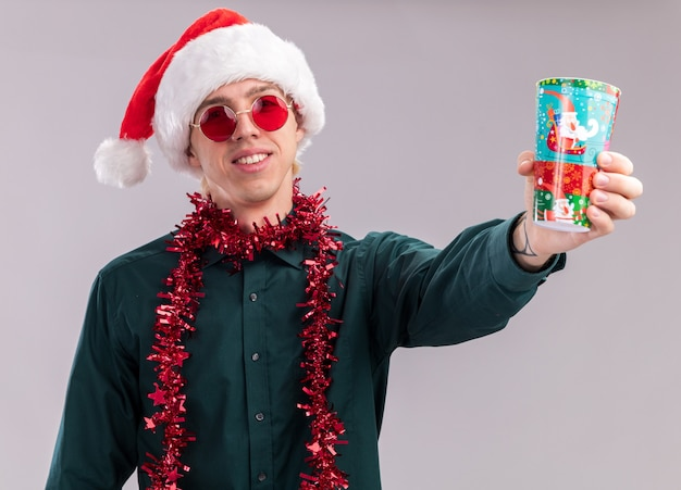 Smiling young blonde man wearing santa hat and glasses with tinsel garland around neck stretching out plastic christmas cup towards camera looking at camera isolated on white background