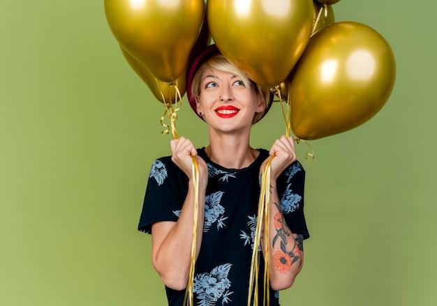 Sorridente giovane bionda party girl holding palloncini guardando lato isolato su sfondo verde oliva con spazio di copia