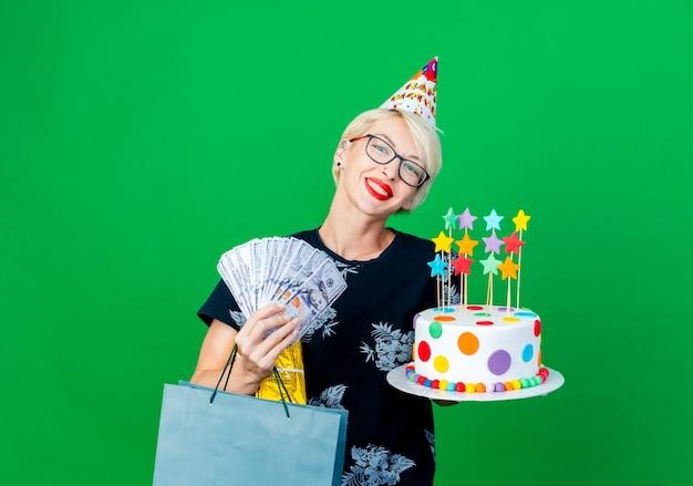 コピースペースで緑の背景に分離されたカメラを見て星のお金のギフトボックスと紙袋と誕生日ケーキを保持しているメガネと誕生日キャップを身に着けている若いブロンドのパーティーの女の子